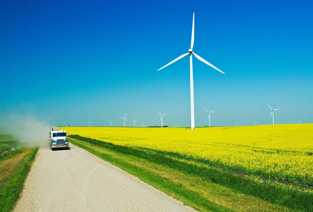 A truck travels down a country road overlooking a blooming canola field and wind turbines, Tiger Hills, Manitoba, Canada : Stock Photo