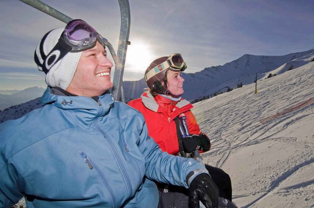 Stock Photo: 1990-50818 A couple takes in the view on a beautiful day while riding the chairlift at Marmot Basin Ski Resort near Jasper, Alberta Canada