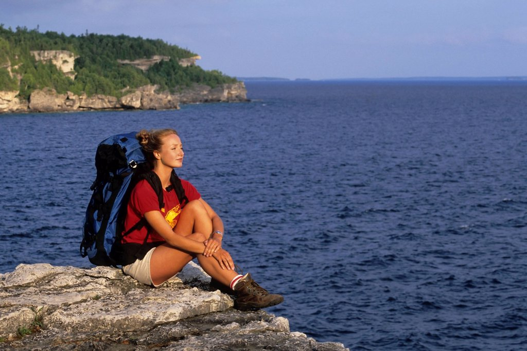 A young woman backpacker rests on an overlook of the Niagara Escarpment along the Bruce Trail, Bruce Peninsula National Park, Ontario, Canada. : Stock Photo