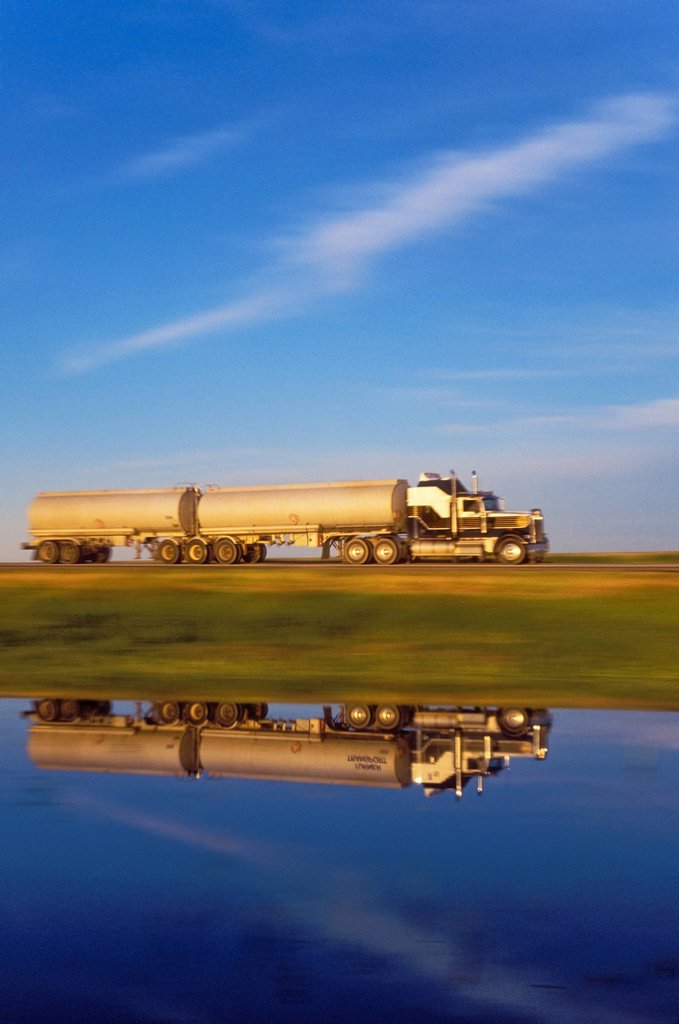 Stock Photo: 1990-51256 Transport truck casts reflection in pond as it carries goods across the Canadian Prairies on the Trans_Canada Highway, Saskatchewan, Canada.