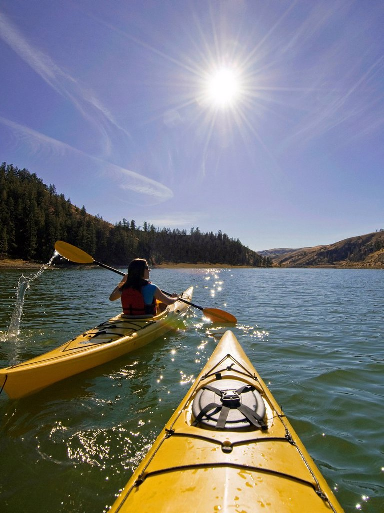 Young woman kayaking on a stunning day at Trapp Lake near Kamloops, British Columbia, Canada : Stock Photo