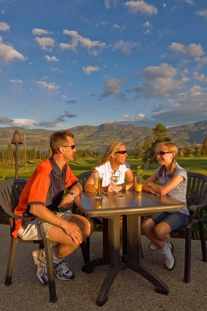 A family relaxing after a round of golf at outdoor clubhouse restaurant, Two Eagles Golf Course in Westbank, British Columbia, Canada : Stock Photo