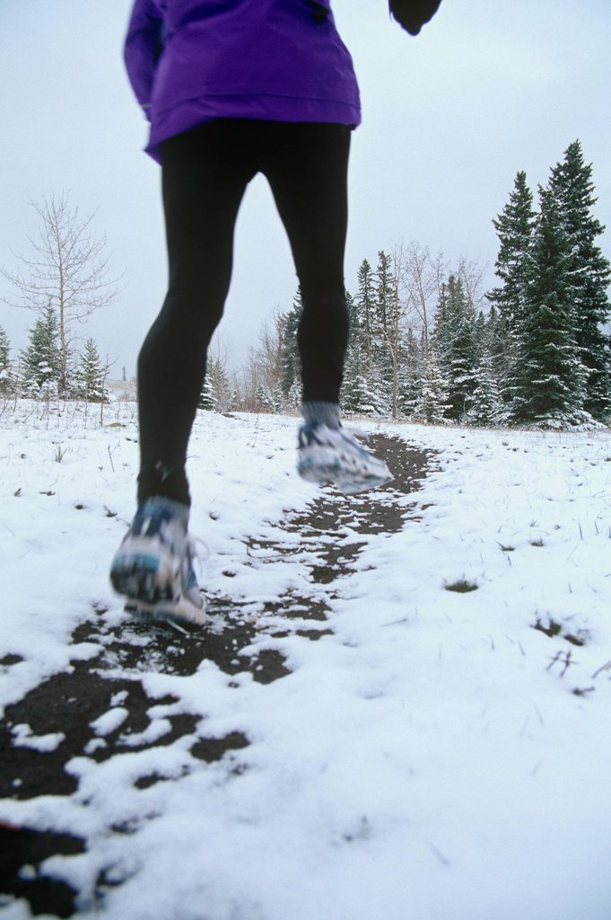 Stock Photo: 1990-52368 Woman running in winter, Canmore, Alberta, Canada.
