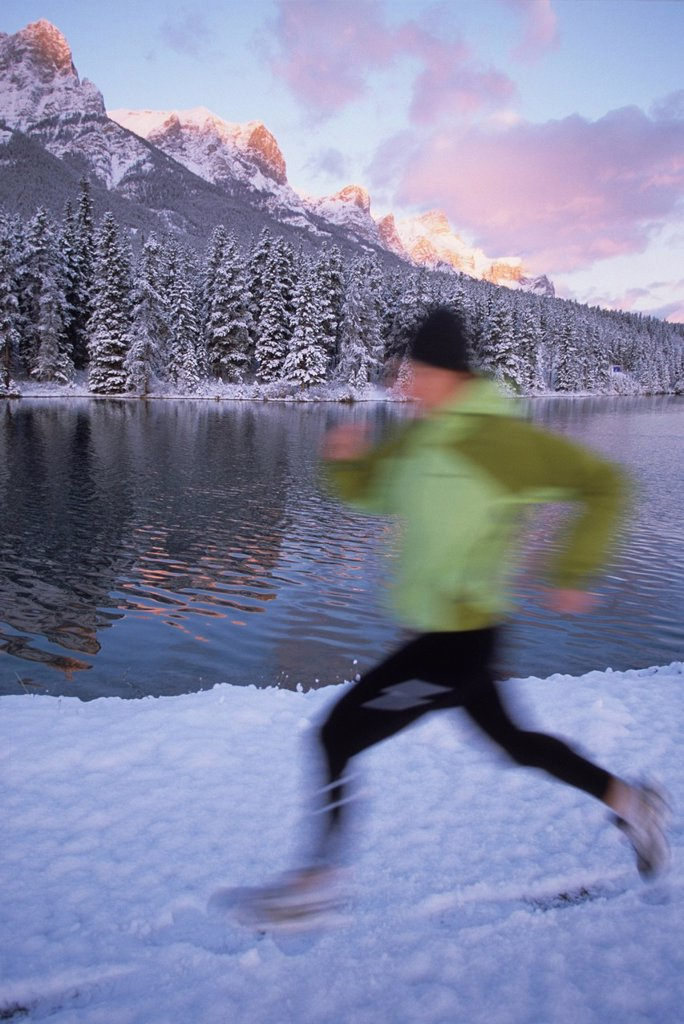 a young woman trail running in the winter on fresh snow in Canmore, Alberta, Canada. : Stock Photo