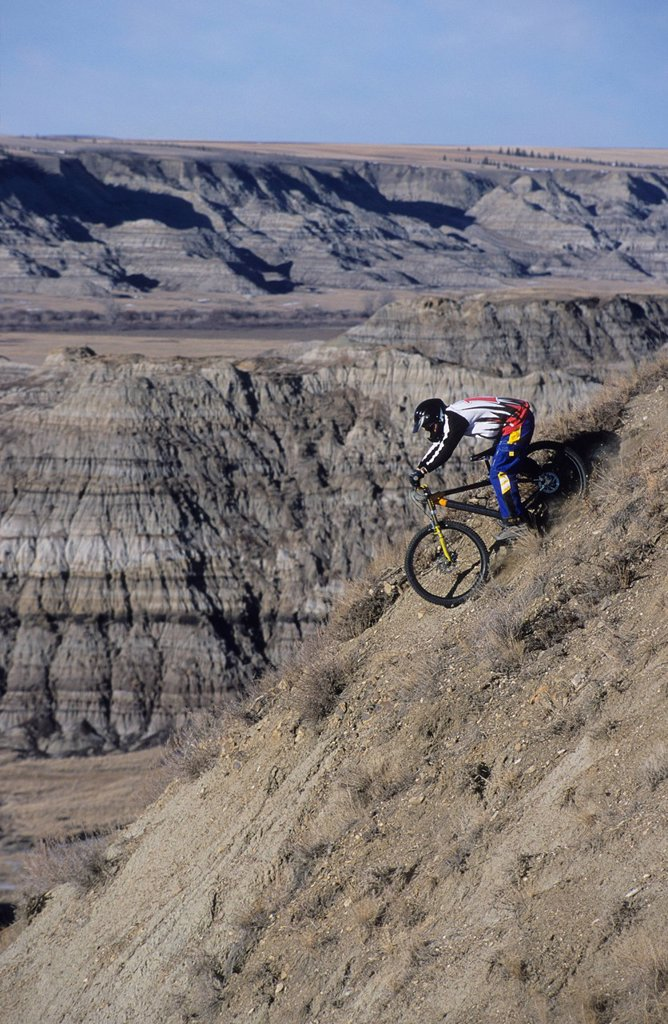 A young man descending on a steep pitch in the badlands in Drumheller, Alberta, Canada. : Stock Photo