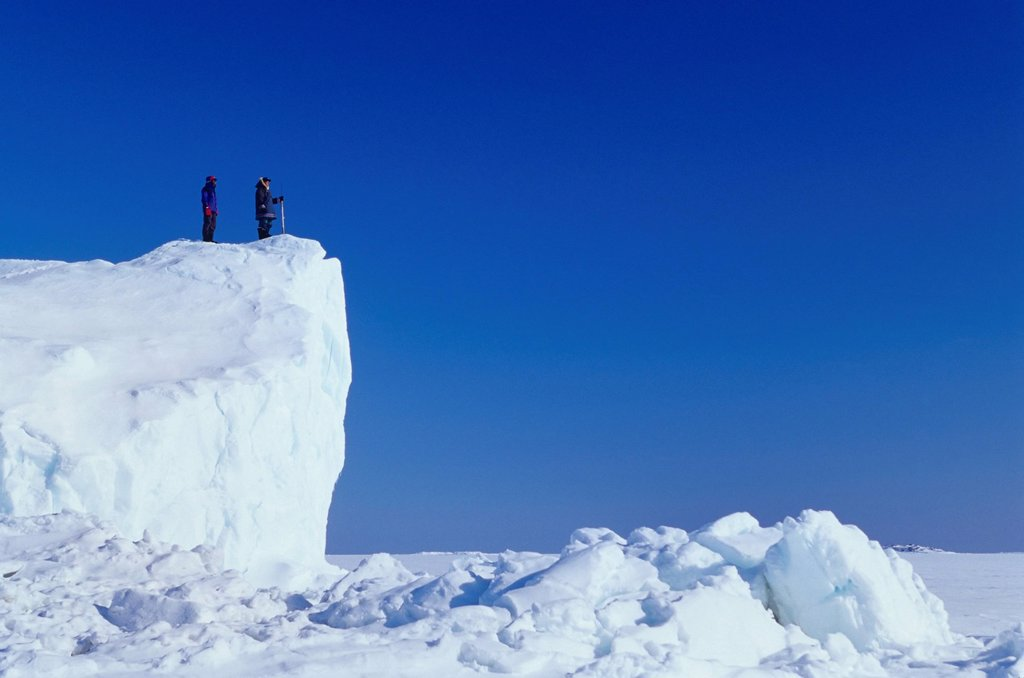 Inuit guide and client on iceberg frozen in sea ice, Kimmirut, Baffin Island, Nunavut, Canada. : Stock Photo