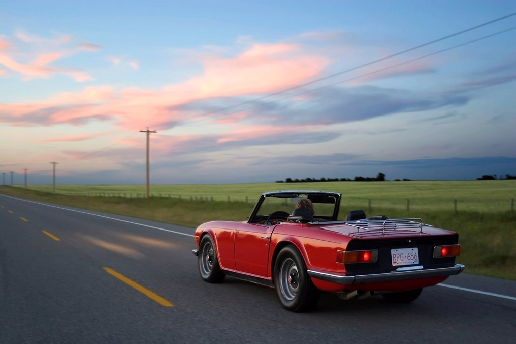 Woman driving red sports car on rural highway, High River, Alberta, Canada. : Stock Photo