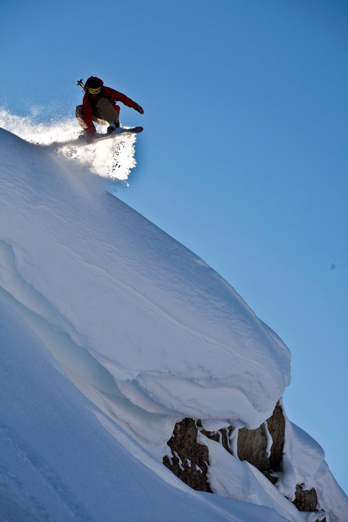 Stock Photo: 1990-55222 A backcountry snowboarder launches a cornice, Healy Pass, Banff National Park, Alberta, Canada