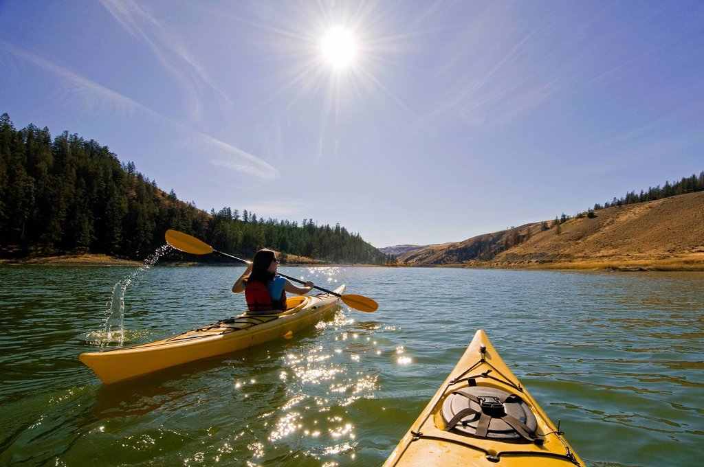 Stock Photo: 1990-55870 Young woman kayaking on a stunning day at Trapp Lake near Kamloops, British Columbia, Canada