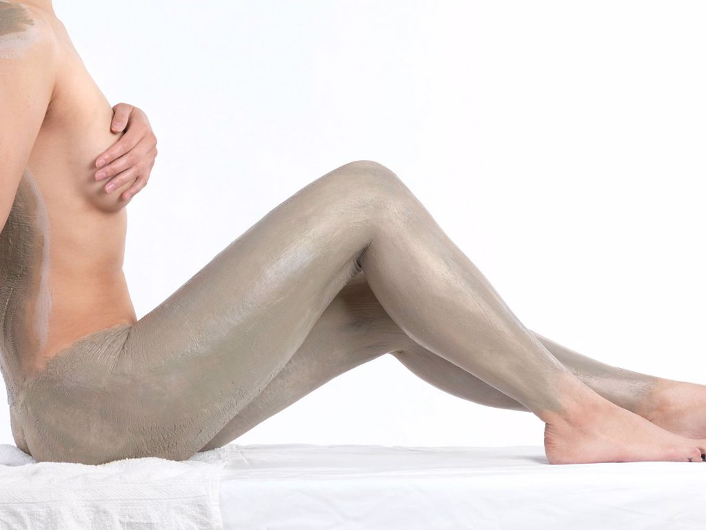 Woman with bentonite clay body wrap mask on her legs and back : Stock Photo