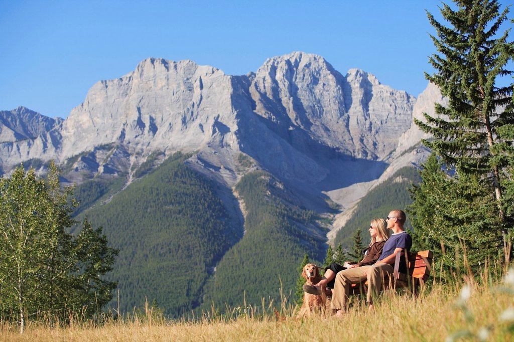 Husband and wife man and woman sitting on a park bench with their dog in the Canadian Rocky Mountains in Canmore, Alberta, Canada. : Stock Photo