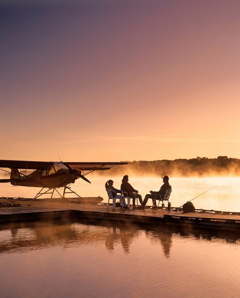 Stock Photo: 1990-56187 Silhouette of family sitting on float plane dock in the morning, Red River, Manitoba, Canada