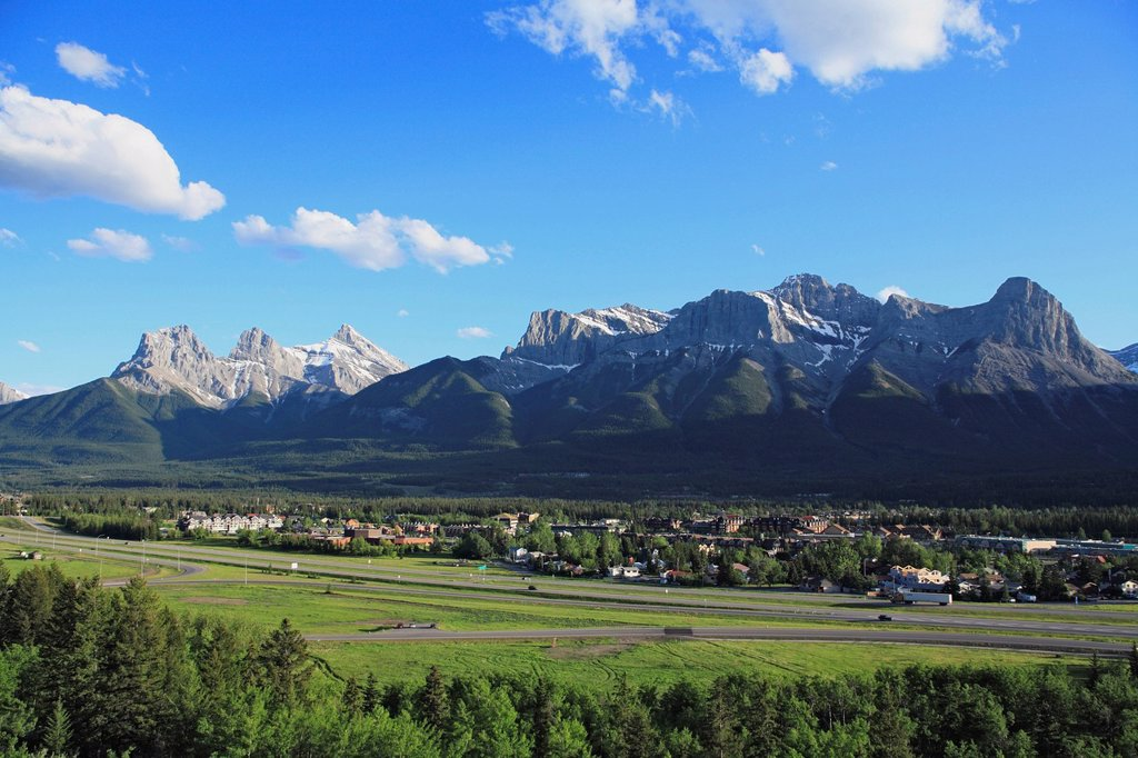 Stock Photo: 1990-56480 The Trans_Canada Highway runs through the Bow Valley and the town of Canmore beneath the Three Sisters mountains in Alberta, Canada