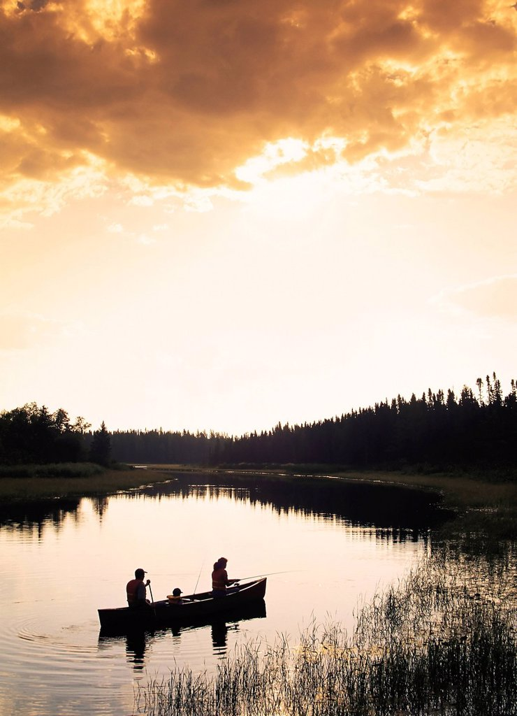 Silhouette of family canoeing and fishing, Whiteshell River, Whiteshell Provincial Park, Manitoba, Canada : Stock Photo