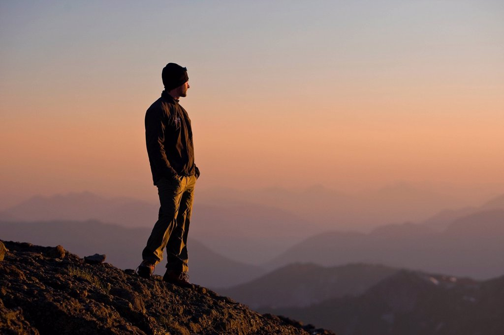 Stock Photo: 1990-56711 A lone mountain climber stands atop King´s Peak and enjoys the last rays of the setting sun, Strathcona Park, Central Vancouver Island, British Columbia, Canada