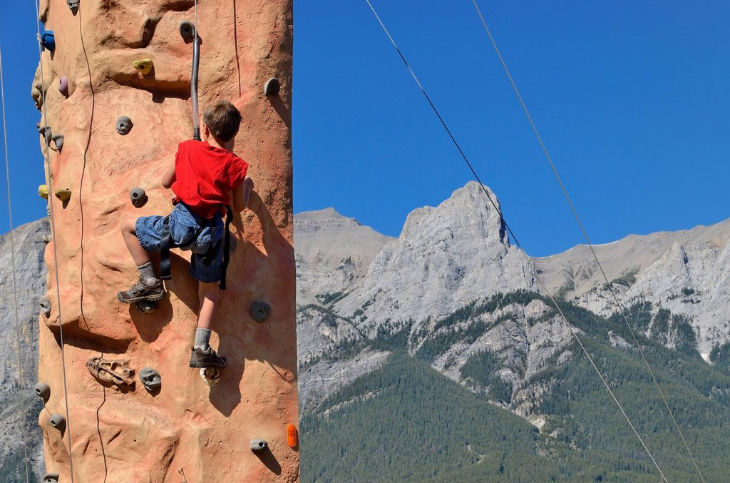 Young boy on climbing wall with mountains in background, Canmore, Alberta, Canada : Stock Photo