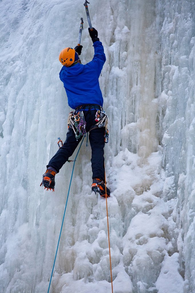 A young man climbs some steep ice, La Mer de Glace 4+, near St Raymond, Quebec, Canada : Stock Photo