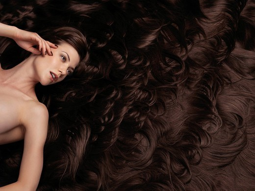 Beautiful woman with very long brown hair and hair extensions. Large copyspace or background. : Stock Photo