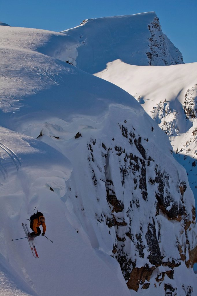 Stock Photo: 1990-58048 A male skier drops off a cornice in the, Kicking Horse Backcountry, Golden, British Columbia, Canada