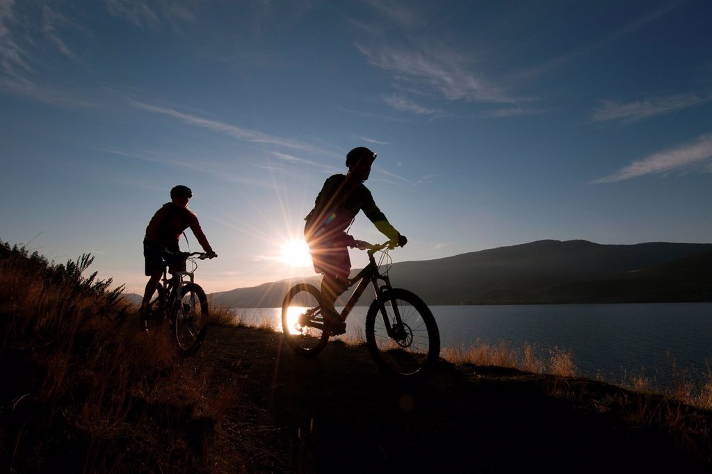 A pair of mountain bikers enjoy a ride at sunset on the trails of Knox mountain, beside Okanagan Lake, in Kelowna, Thompson Okanagan region of British Columbia, Canada : Stock Photo