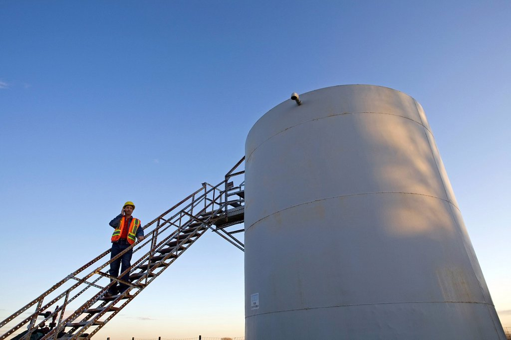 Oil industry worker on storage tank platform talking on phone. : Stock Photo