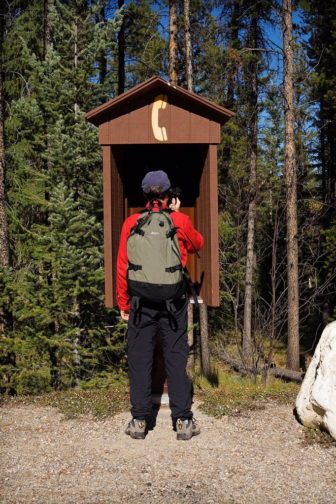 Stock Photo: 1990-59112 Hiker calling on outdoor pay phone, Jasper National Park, Alberta, Canada.