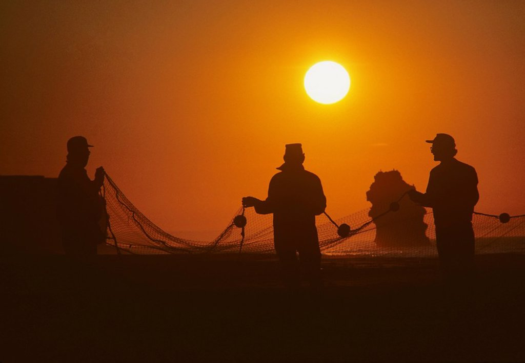 Stock Photo: 1990-5940 Gaspereau fishermen in sunset, Cousin´s Shore Beach, Prince Edward Island, Canada