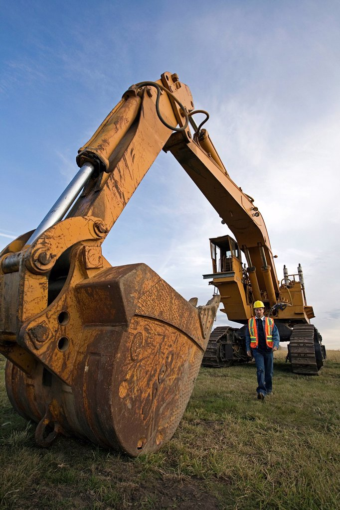 Stock Photo: 1990-59716 Heavy equipment operator walking next to excavating machine.