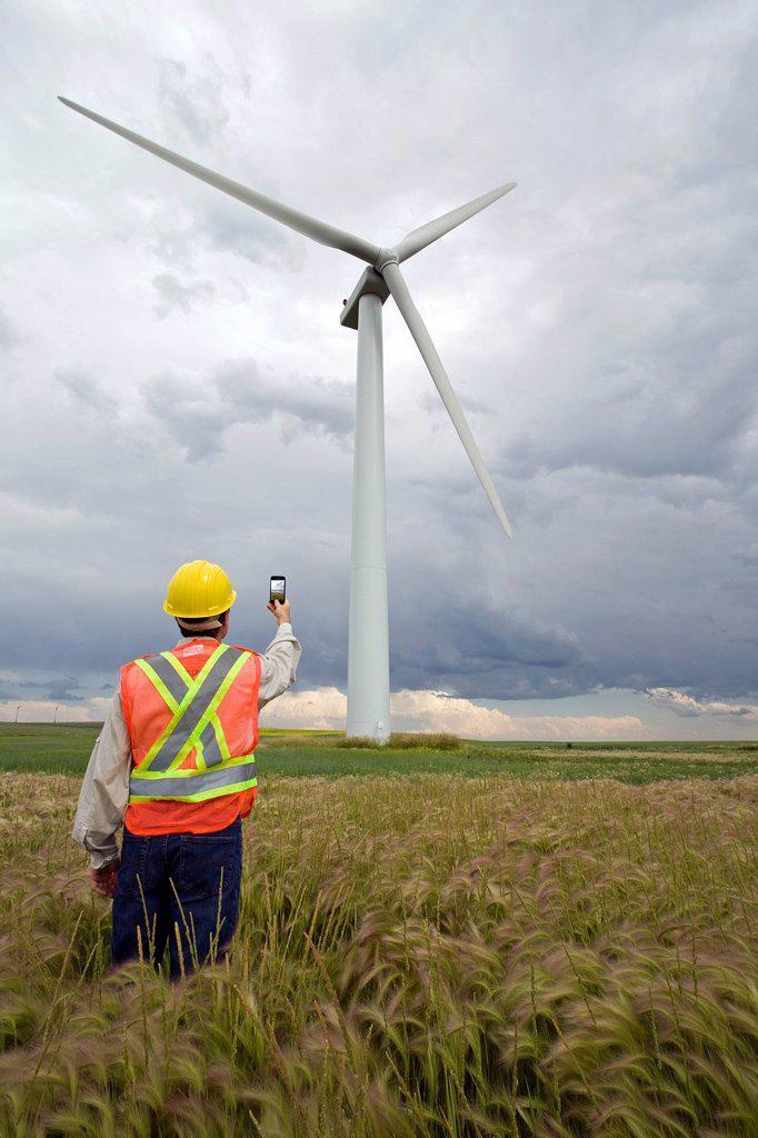 Wind power technician standing next to wind turbine, near Pincher Creek, Alberta. : Stock Photo