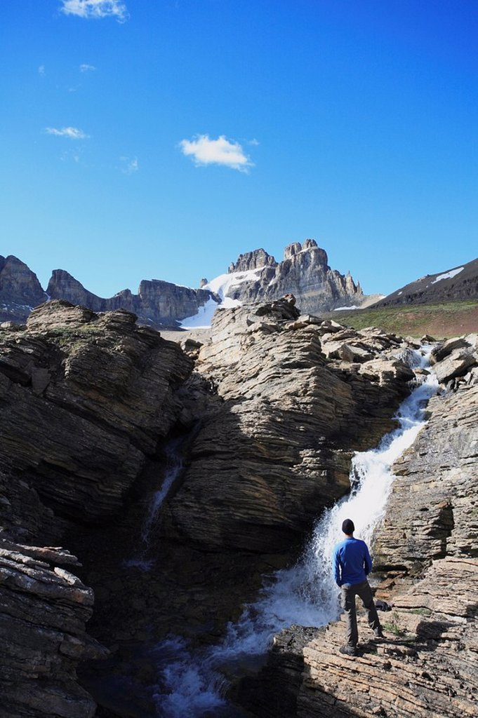 Stock Photo: 1990-6058 Hiker looking at a waterfall on Dolomite Creek with Dolomite Peak in the background, Banff National Park, Alberta, Canada