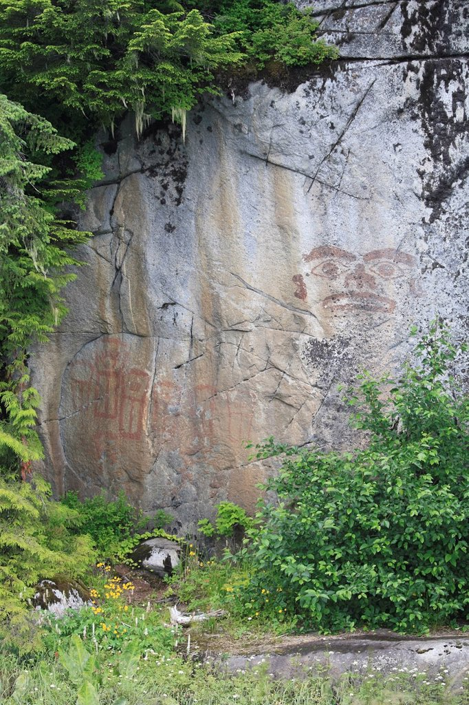 Stock Photo: 1990-61185 Images of a face and seven coppers, painted in red ochre on a vertical rock wall were an ´advertisement´ for a local chief from the Tyee area of the lower Skeena River,BC