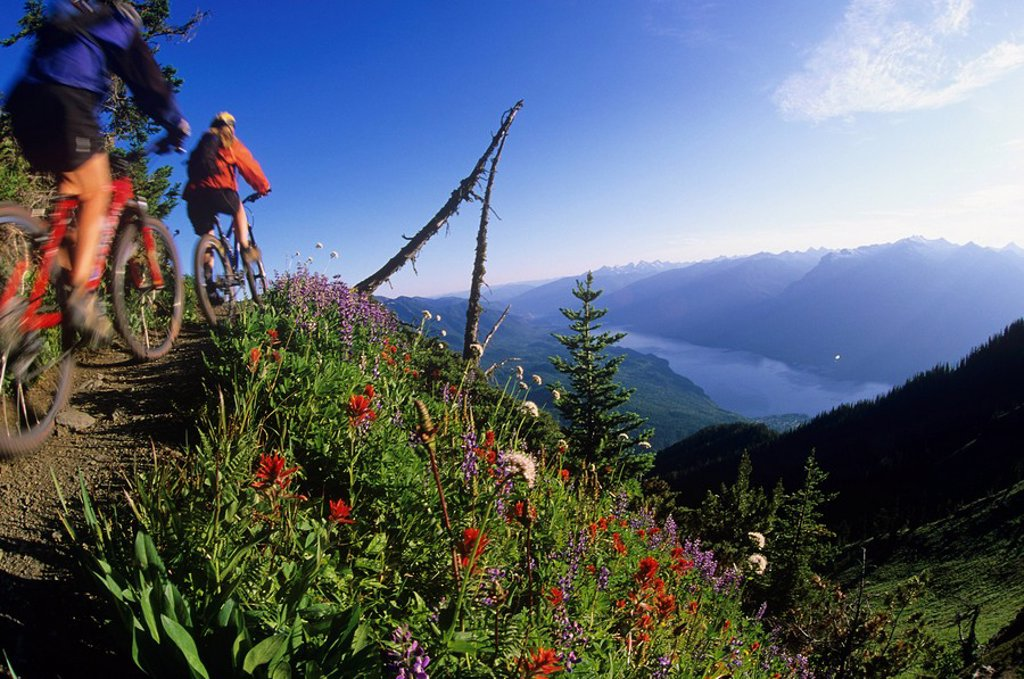 Stock Photo: 1990-6241 Two woman mountain bikers on Idaho Peak with Valhallas behind, Slocan Valley, Kootenays, British Columbia, Canada