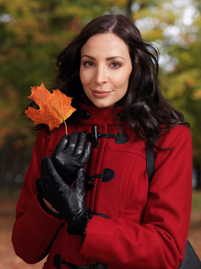 Portrait of a beautiful woman holding a red maple leaf in her hands : Stock Photo
