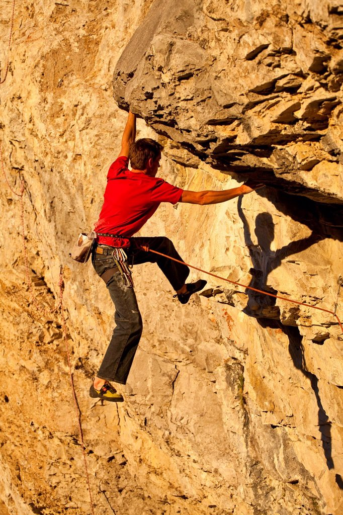 A man climbs the sport route Fire in the Sky 12b at sunset, Echo Canyon, Canmore, Alberta, Canada : Stock Photo