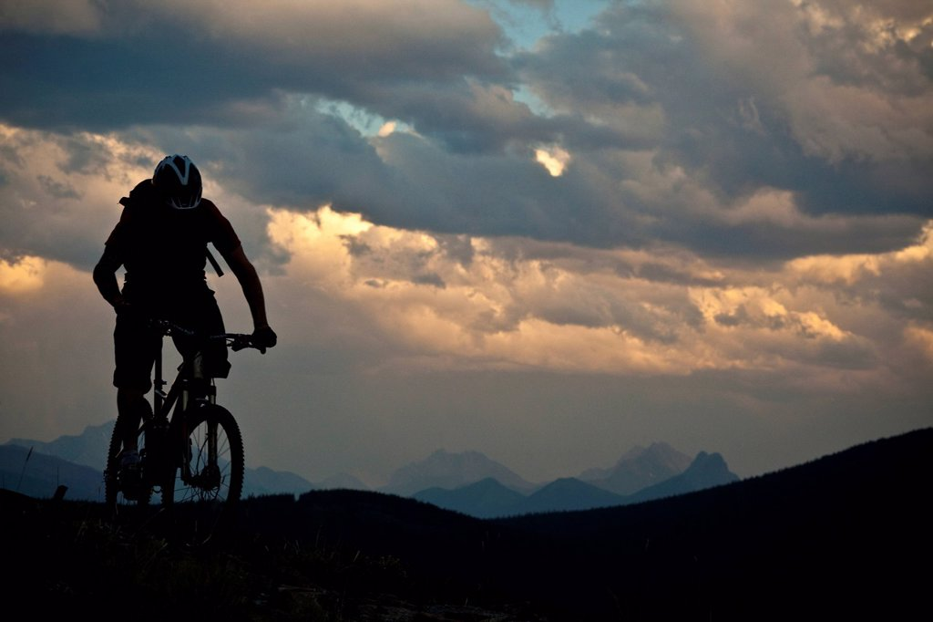 A male mountain biker riding at ridgetop at sunset. Canmore, Alberta, Canada : Stock Photo