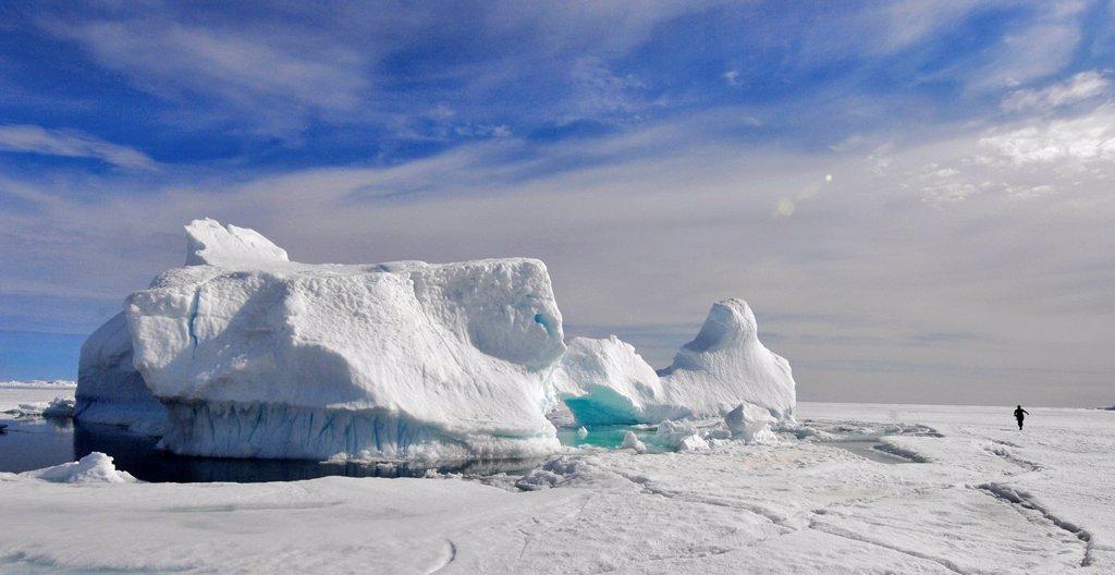 Person running beside Iceberg, Nunavut, Baffin Island : Stock Photo
