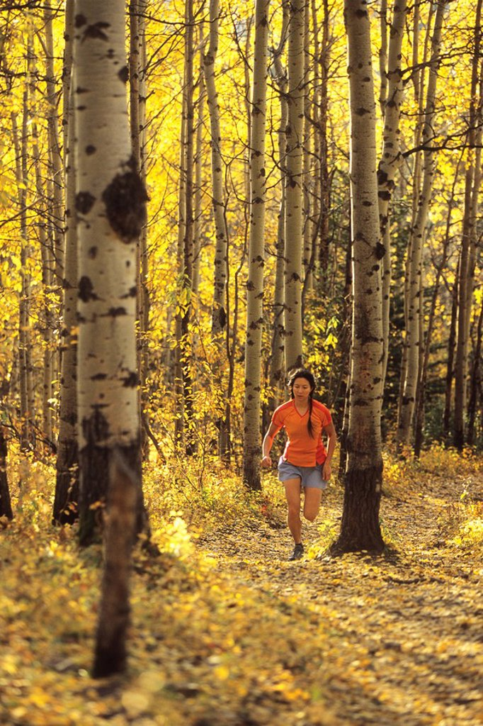 Stock Photo: 1990-6445 young asian woman trail running below Mt Yamnuska, Kananaskis, Alberta, Canada