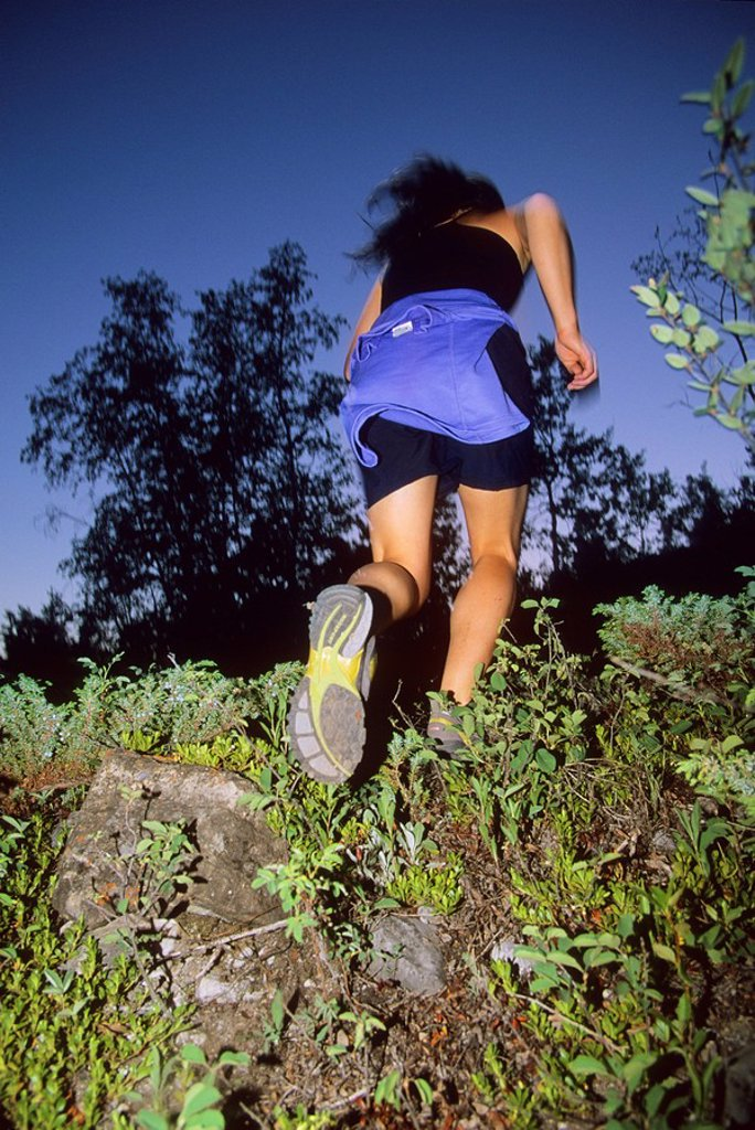 Stock Photo: 1990-6449 a young woman trail running at dusk in Canmore, Rocky Mountains, Canmore, Alberta, Canada
