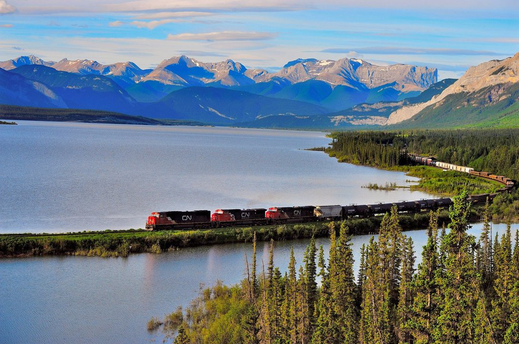 Stock Photo: 1990-65379 A Canadian National freight train traveling along Brule Lake in the foothills of the Rocky Mountains of Alberta Canada.