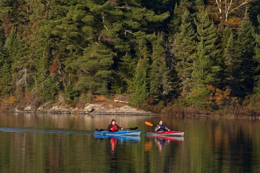 Middle_aged couple enjoy early morning paddle in kayaks on Source Lake, Algonquin Park, Ontario, Canada. : Stock Photo