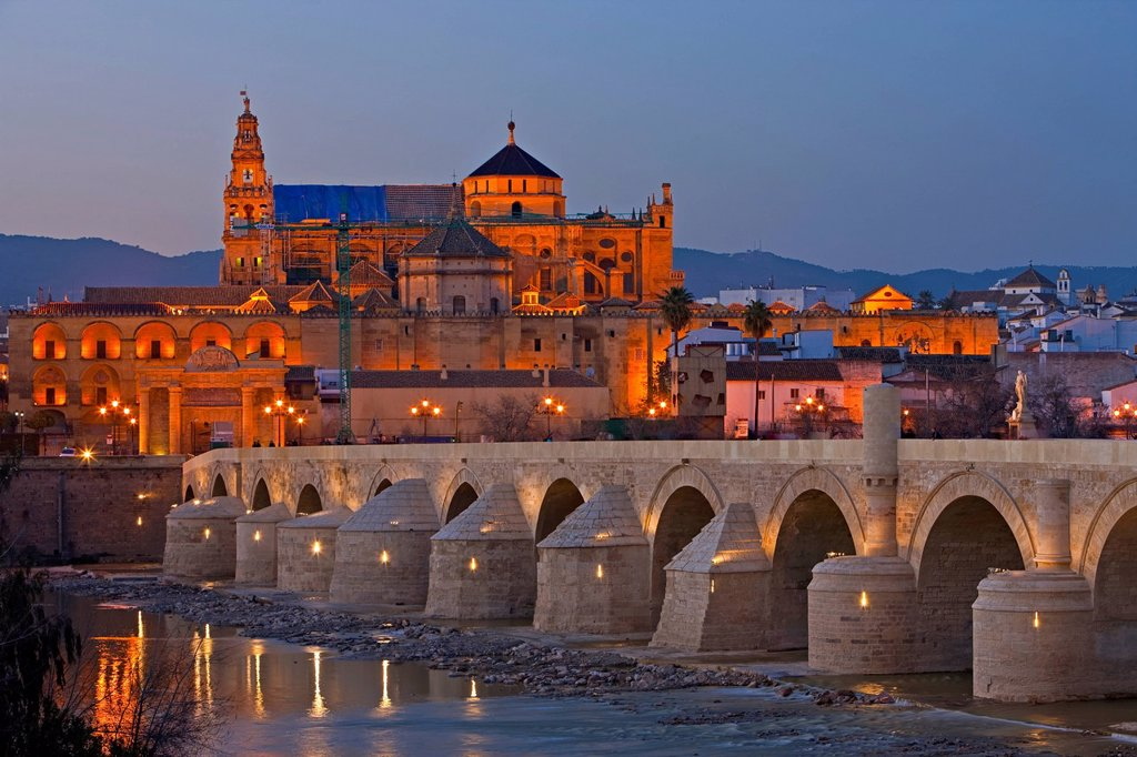 Puente Romano bridge spanning the Rio Guadalquivir river and the Mezquita Cathedral_Mosque during dusk in the City of Cordoba, UNESCO World Heritage Site, Province of Cordoba, Andalusia Andalucia, Spain, Europe. : Stock Photo