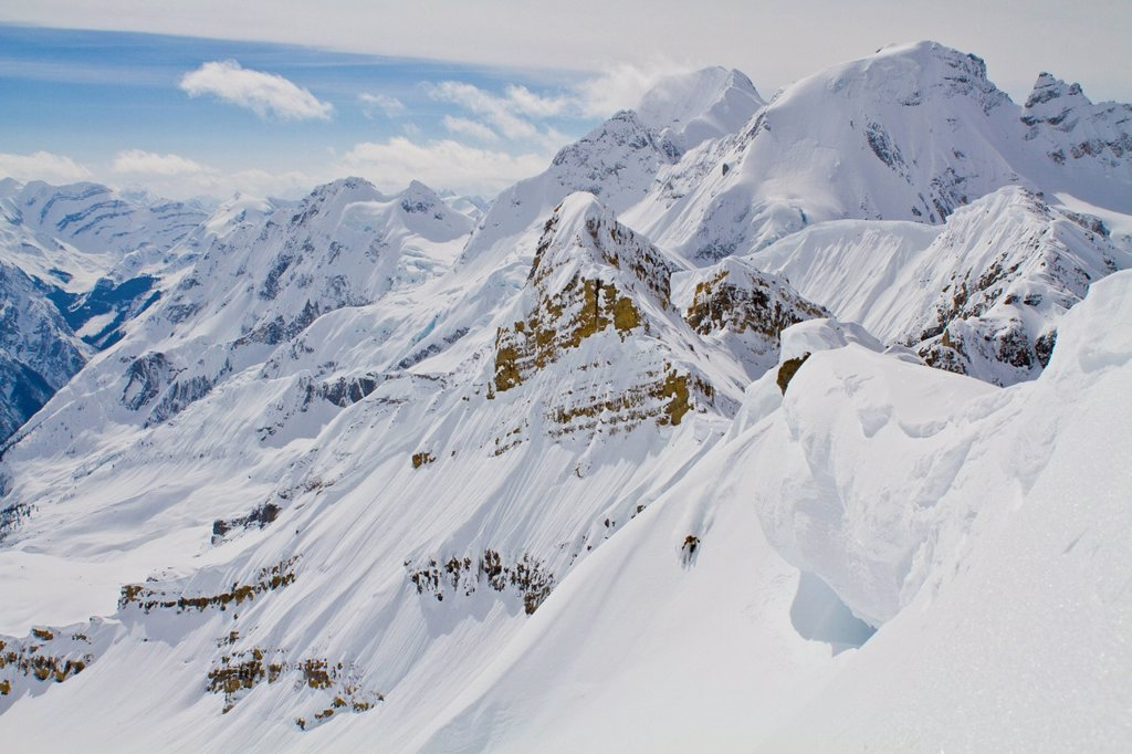 A male backcountry skiers rips a big line under a giant cornice in the Candian Rockies. Icefall Lodge, Golden, BC : Stock Photo