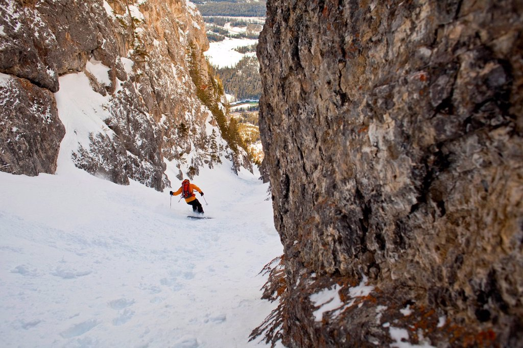 A male backcountry skier rips down a steep coulior close to downtown Banff. Mt. Cory, Banff National Park, AB : Stock Photo