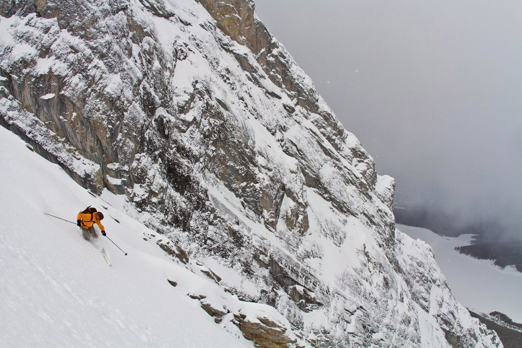 A male backcountry telemark skier heads down a steep couloir in Spray Lakes, Kananaskis, near Canmore AB : Stock Photo
