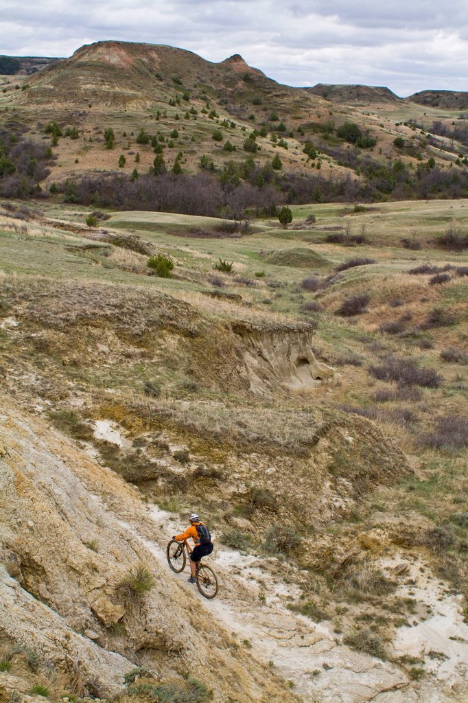 Stock Photo: 1990-67050 A female mountain biker follows a perfect ribbon of singletrack. Maah Daah Hey Trail, North Dakota