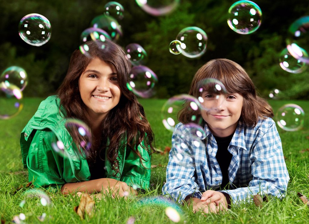 Stock Photo: 1990-67308 Artistic portrait of two happy smiling children, sister and younger brother, lying down on green grass with soap bubbles around them.