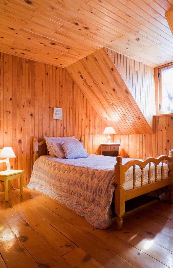 Stock Photo: 1990-70924 Bedroom on the upstairs floor of a Canadiana cottage style residential log home, Laval, Quebec, Canada