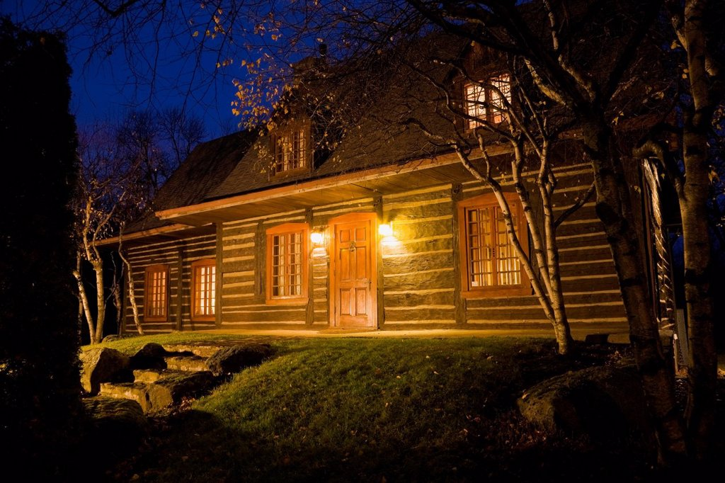 Old 1975 Reconstructed Canadiana Cottage style Residential Log Home illuminated at dusk, Quebec, Canada : Stock Photo