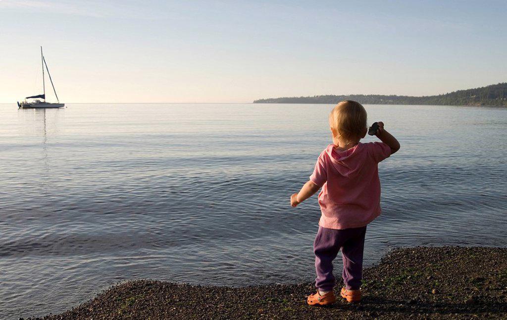 Young girl throws stones on beach near Cordova Bay, Victoria, Vancover Island, British Columbia, Canada : Stock Photo