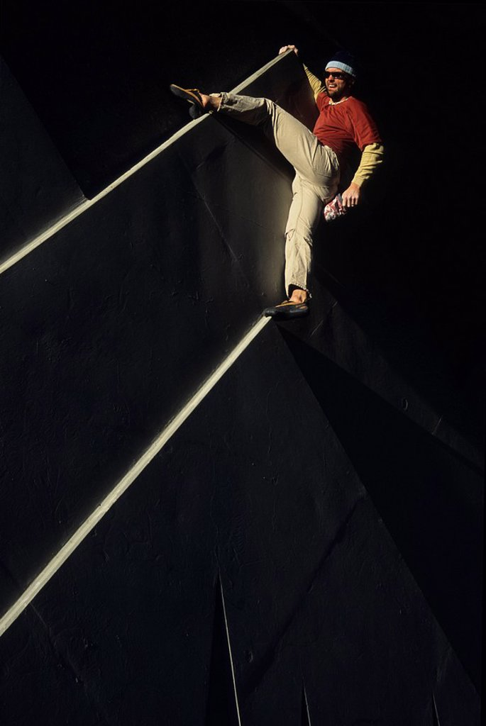 Stock Photo: 1990-7527 A young man free climbing a sign in Canmore, Alberta, Canada